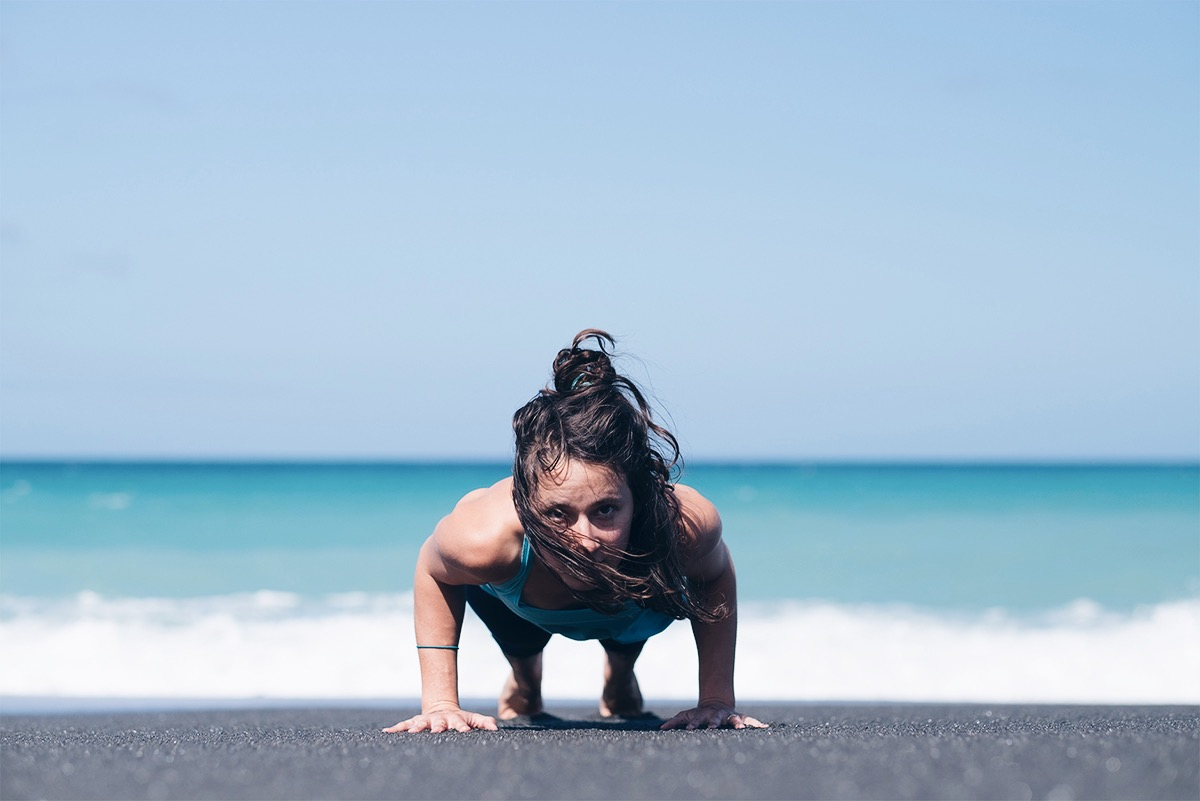 Ilona Barnhart in Chaturanga or low plank yoga pose on black sand beach in New Zealand